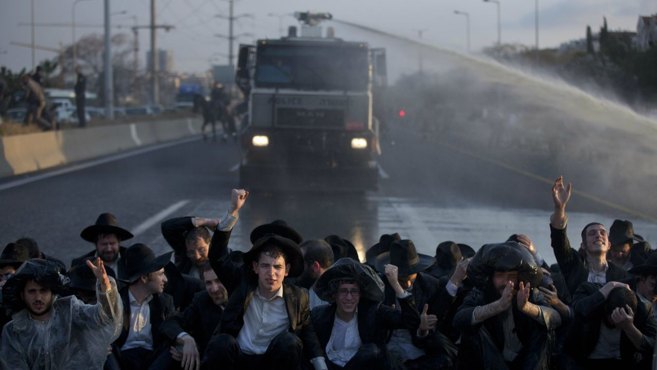 Israeli police uses water cannons with stinky water to disperse Ultra orthodox Jews as they block highway during a protest against the detention of a member of their community who refuses to serve in the the military service, in Bnei Brak, Israel. (AP/PTI)