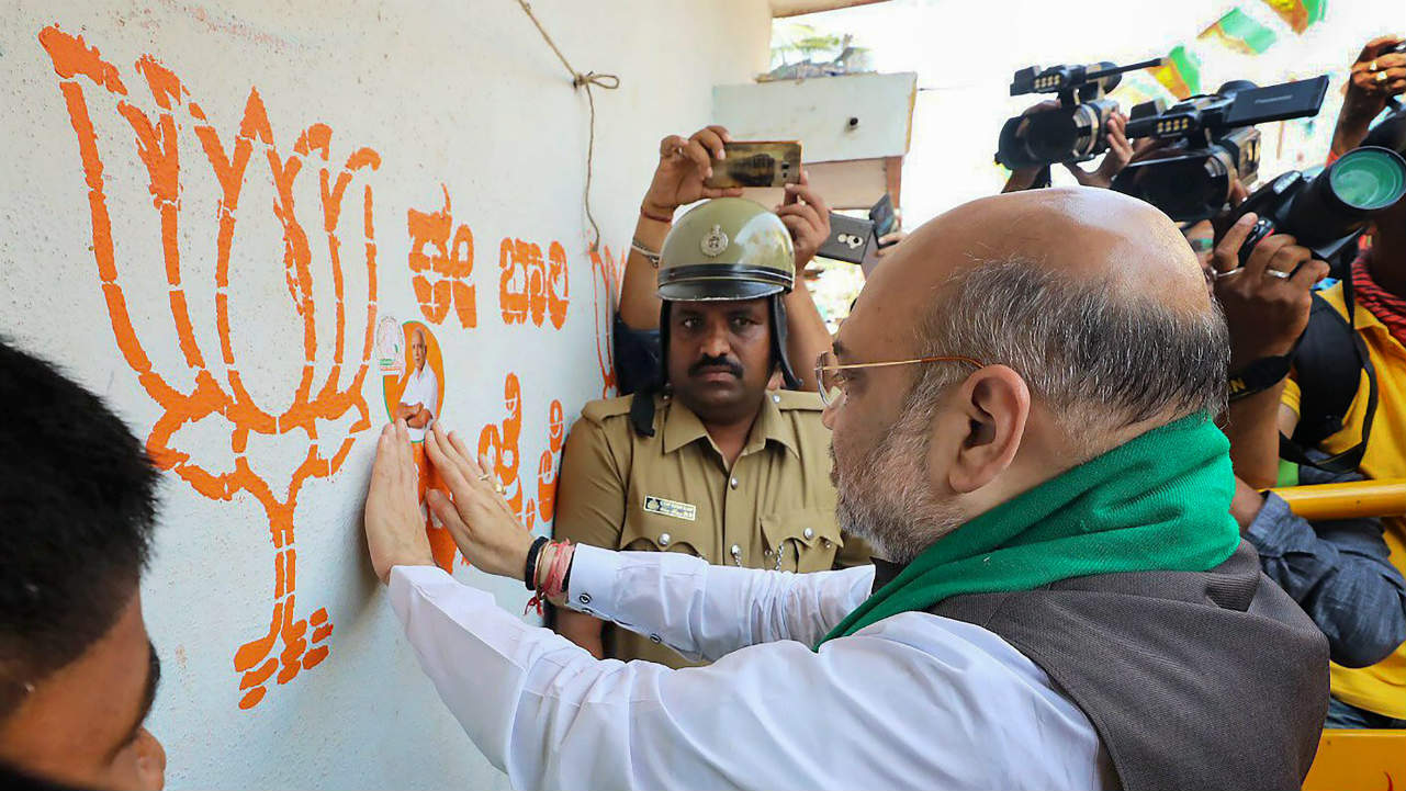 BJP National President Amit Shah during a statewide door-to-door campaign 'Mushti Dhanya Sangrah Abhiyana', ahead of Karnataka Assembly Elections at Doddabathi village in Davanagere. (PTI)