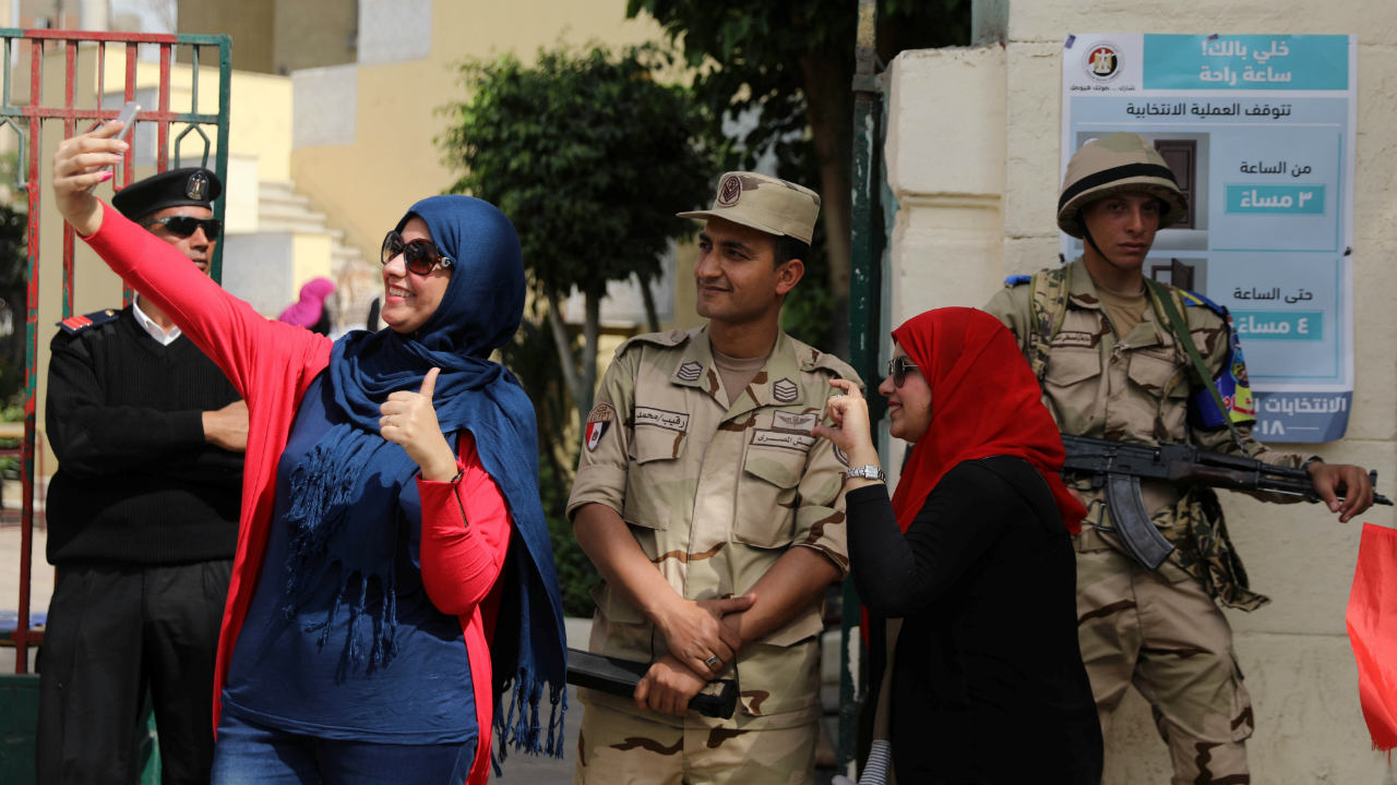 Women take a selfie with an Egyptian soldier as he stands guard outside a polling station during the second day of the presidential election in Cairo, Egypt. (Reuters)