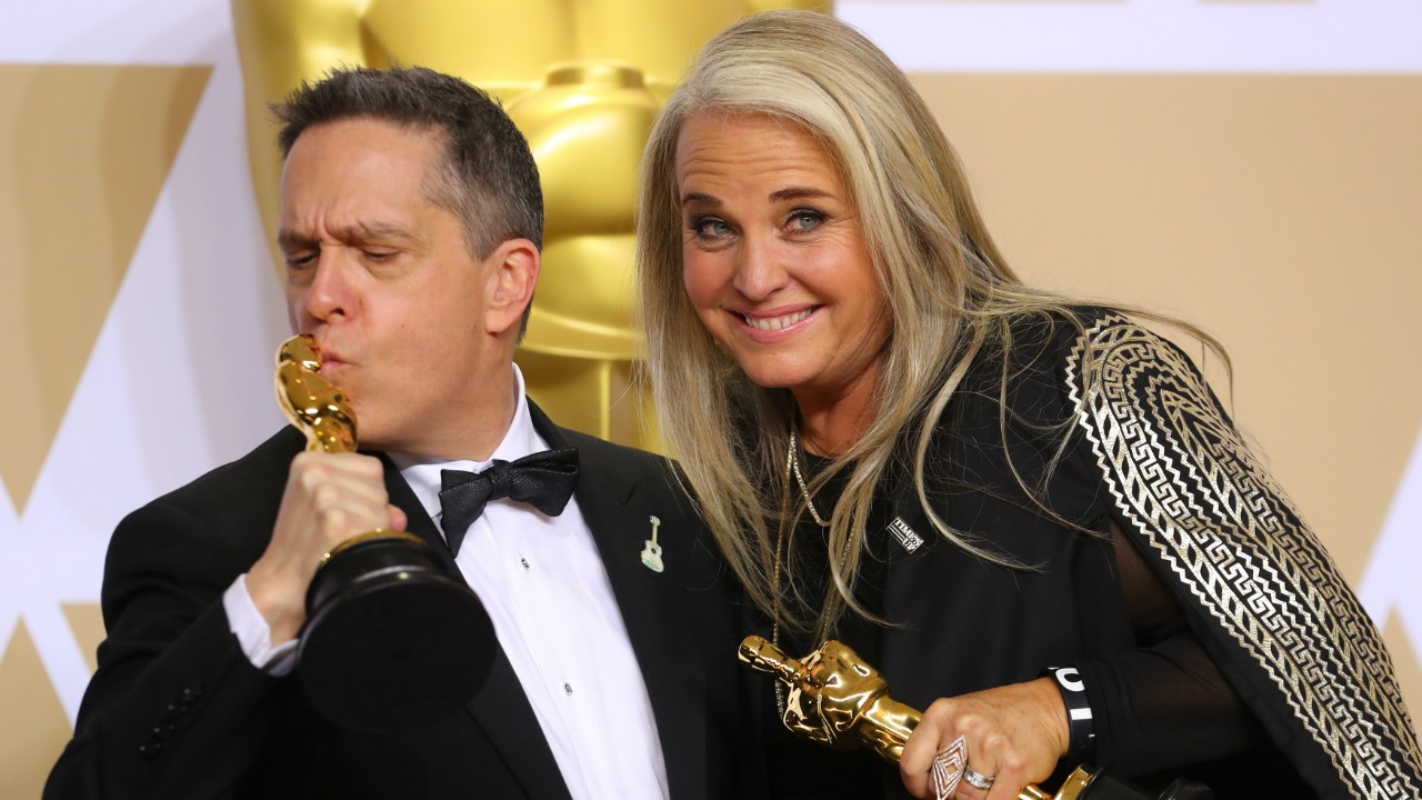 "Lee Unkrich (L) and Darla K. Anderson hold their Oscars for Best Animated Feature Film ""Coco"".(Reuters)"
