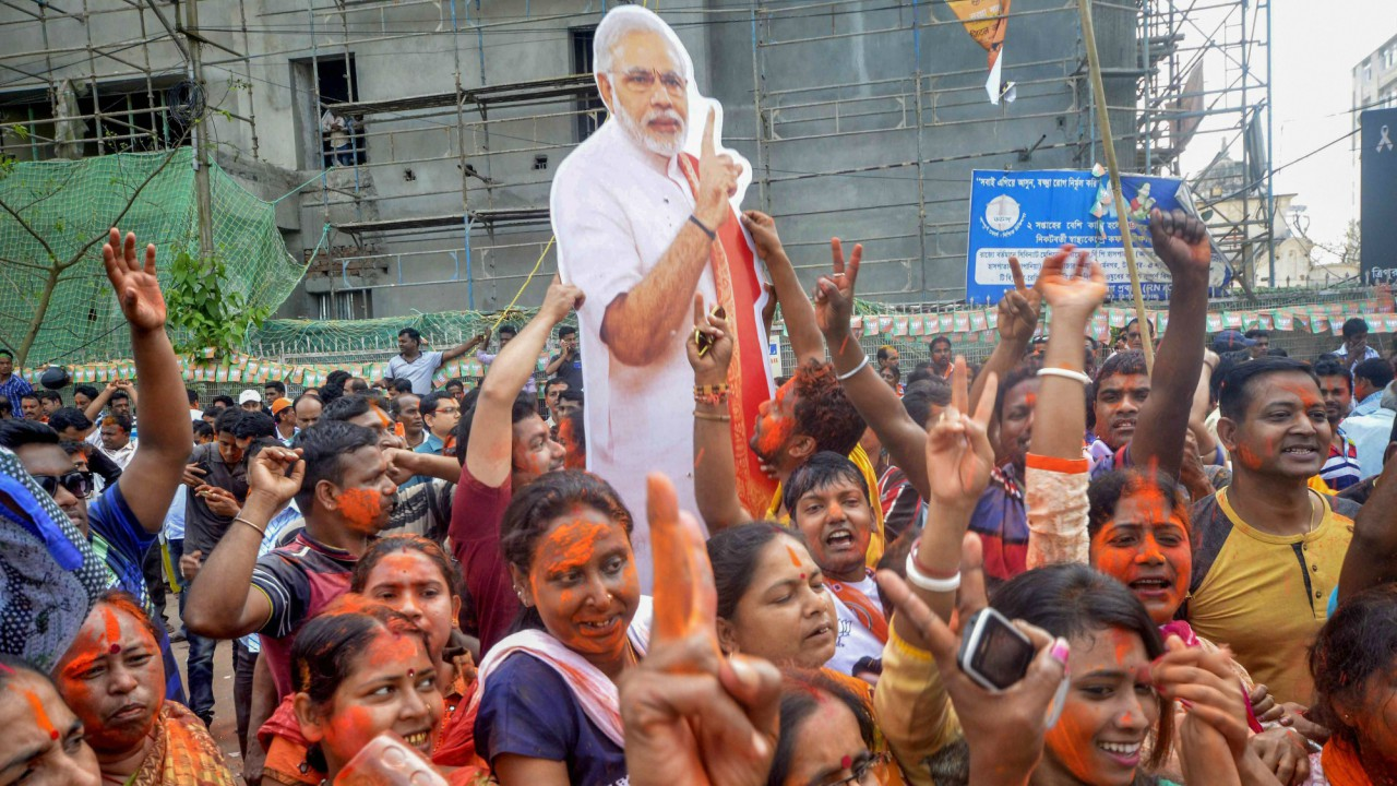 BJP supporters hold up a placard of Prime Minister Narendra Modi after party's victory in Tripura Assembly elections results in Agartala on Saturday. BJP's win marks an end to 25 years of CPI-M government rule in the state. (PTI)