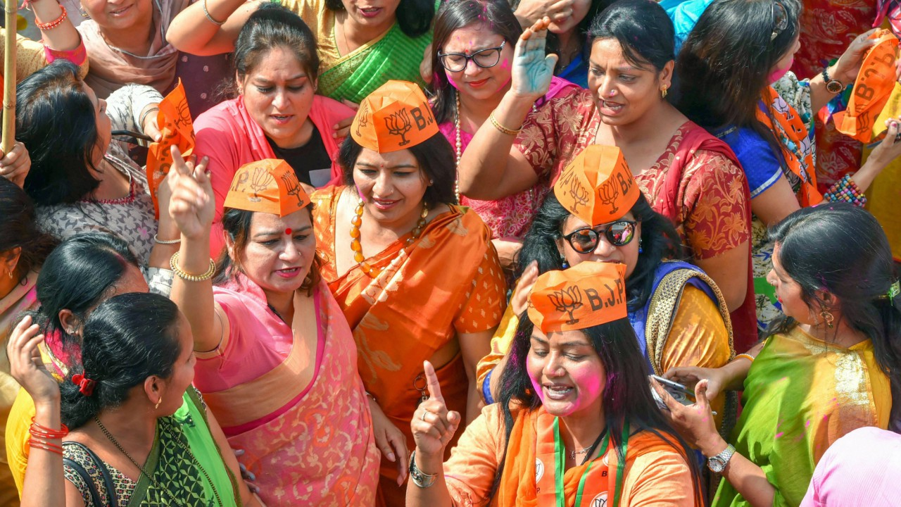 BJP party workers celebrate at party headquarters after Assembly election results, in New Delhi on Saturday. (PTI)