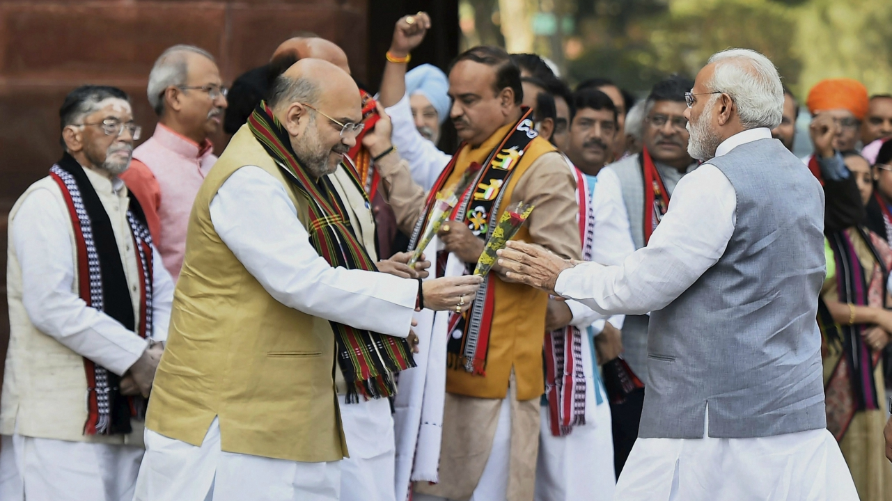 BJP national president Amit Shah greets Prime Minister Narendra Modi as he arrives at the Parliament to attend the second phase of the budget session, in New Delhi on Monday. (PTI)