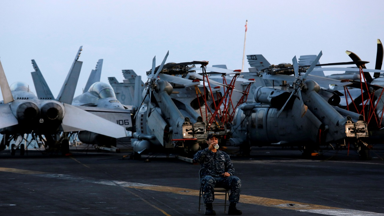 A sailor drinks, as he guards among aircraft, aboard the US Navy aircraft carrier, USS Carl Vinson, after it docked at a port in Danang, Vietnam. (Reuters)