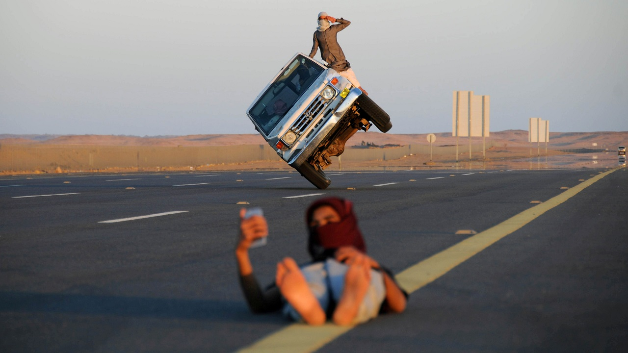 "Saudi men perform a stunt known as ""sidewall skiing"" (driving on two wheels) as a youth takes a selfie in Tabuk, Saudi Arabia. (Reuters)"