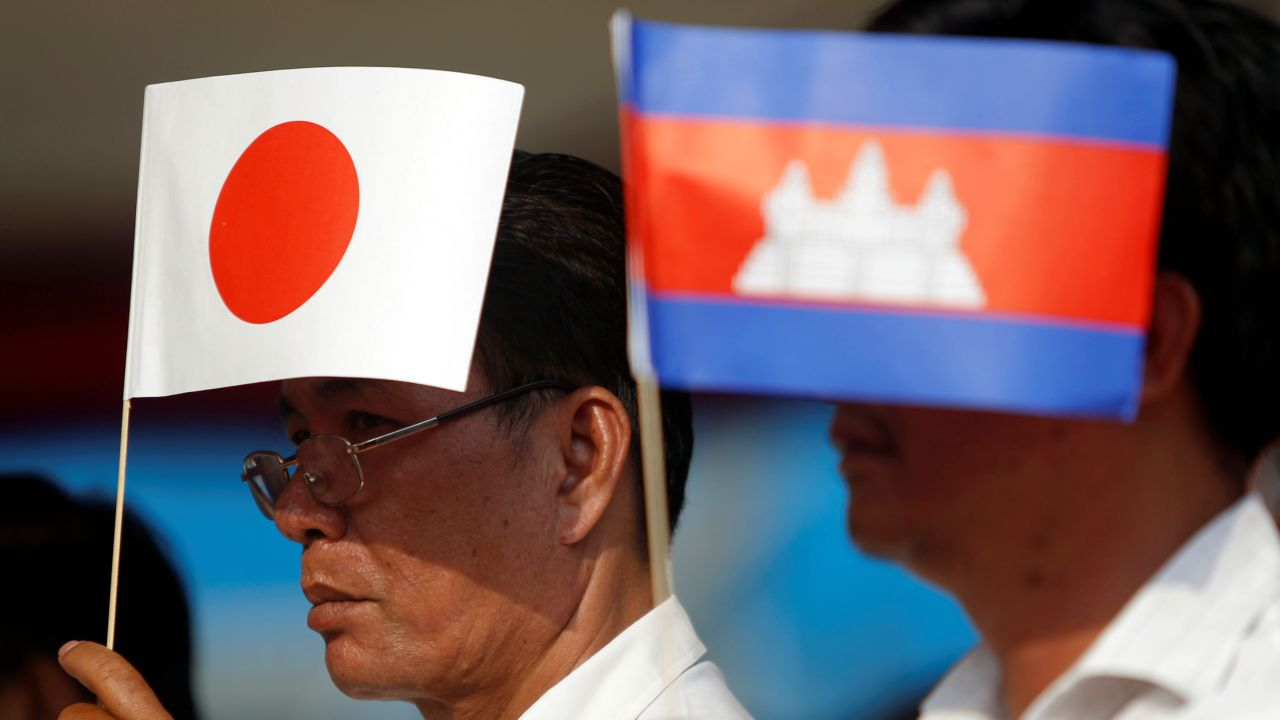 Men hold Cambodian and Japanese flags during the inauguration ceremony of National Road No. 1, which has been built with aid from Japan, in Phnom Penh, Cambodia. (Reuters)