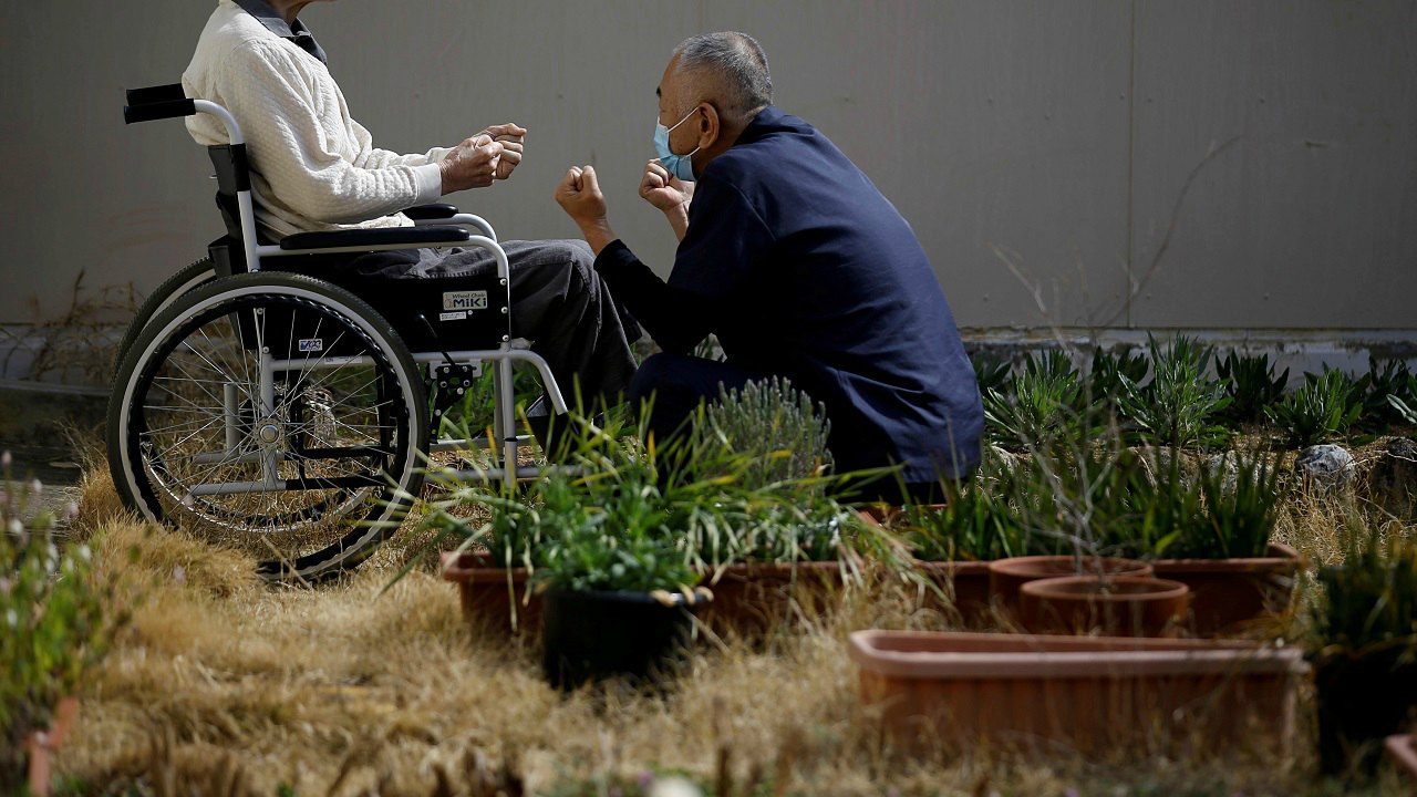 A 92-year-old man in a wheel chair, imprisoned for life in the Tokushima prison, for murder, rape and other offences, exercises with a care worker in a courtyard at the Tokushima prison in Tokushima, Japan. (Reuters)