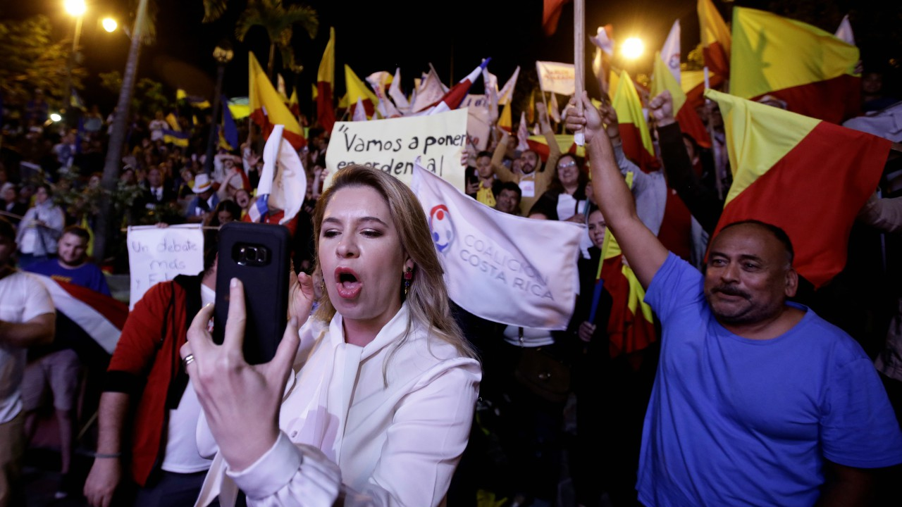 Claudia Dobles wife of Presidential candidate of the ruling Citizens' Action Party (PAC), Carlos Alvarado, make a video from your cell phone during a live televised debate before a second-round presidential election runoff at Supreme Election Tribunal in San Jose, Costa Rica. (REUTERS)
