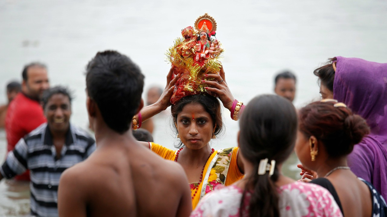 A woman carries an idol of Hindu goddess Durga to immerse it in the Ganges river, after the celebrations of the last day of Navratri festival, in Kolkata. (REUTERS)