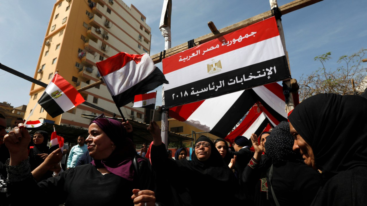 Women holding Egyptian flags celebrate outside a polling station during the presidential election in Cairo, Egypt. (REUTERS)