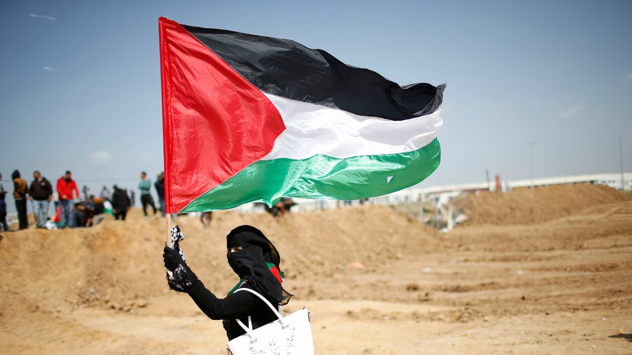 A woman waves a Palestinian flag ahead of a protest in a tent city along Israel border with Gaza, demanding to return to their home land, east of Gaza City. (REUTERS)