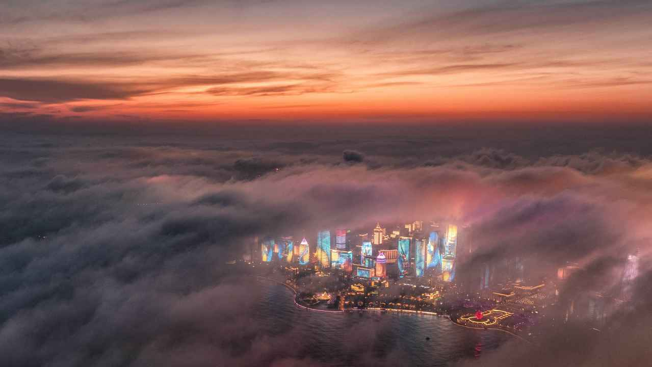 Fog drifts across skyscrapers on the waterfront in Qingdao in eastern China's Shandong Province. A weather system brought clouds and rain to parts of China. (AP/PTI)