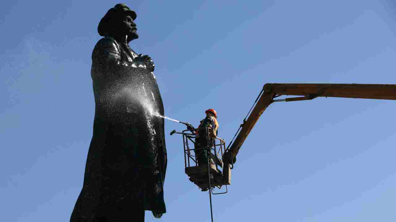 Workers wash a monument to Soviet state founder Vladimir Lenin on the eve of his 148th birth anniversary in Krasnoyarsk, Russia. (REUTERS)