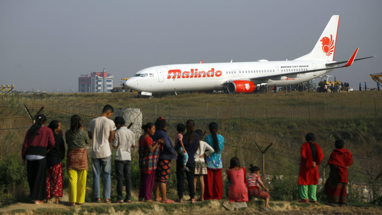 People watch a Malindo Air passenger plane after it skidded to the grassy area at the end of runway in Tribhuwan International Airport in Kathmandu, Nepal. (Image: AP/PTI)