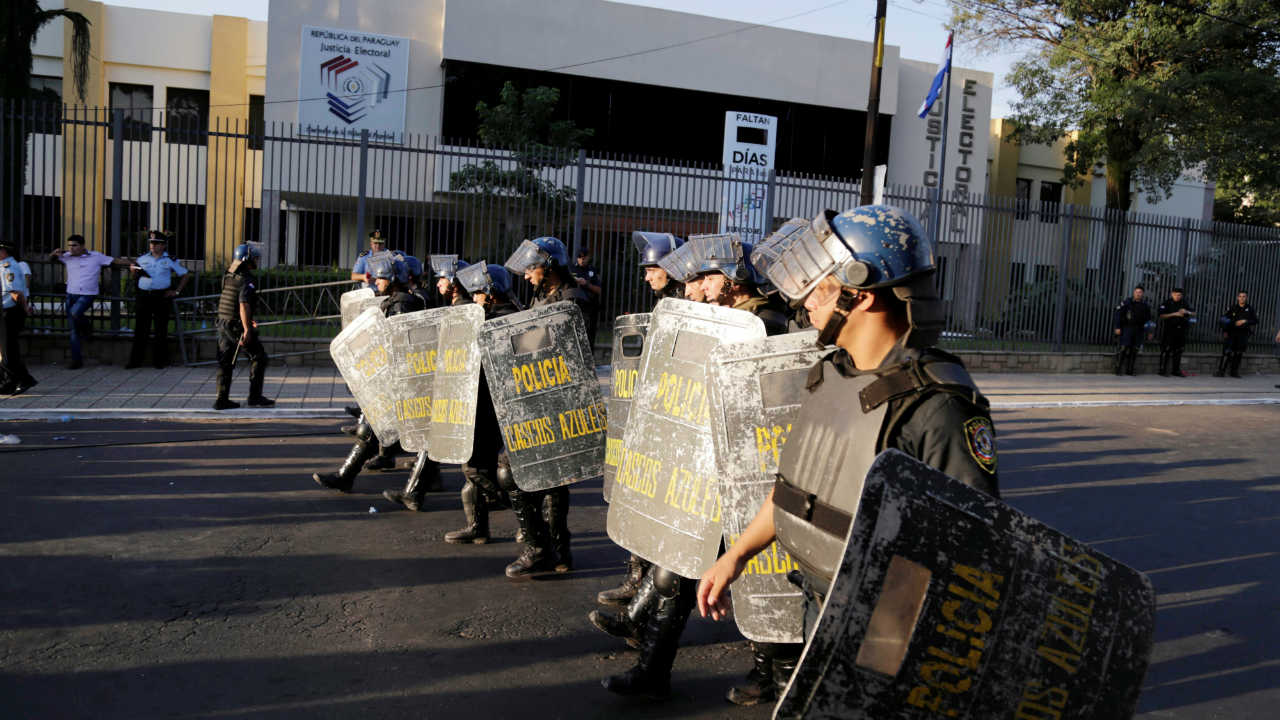Police stand guard as people protest outside the Superior Court of Electoral Justice after Paraguay's presidential election results, in Asuncion, Paraguay. (Reuters)