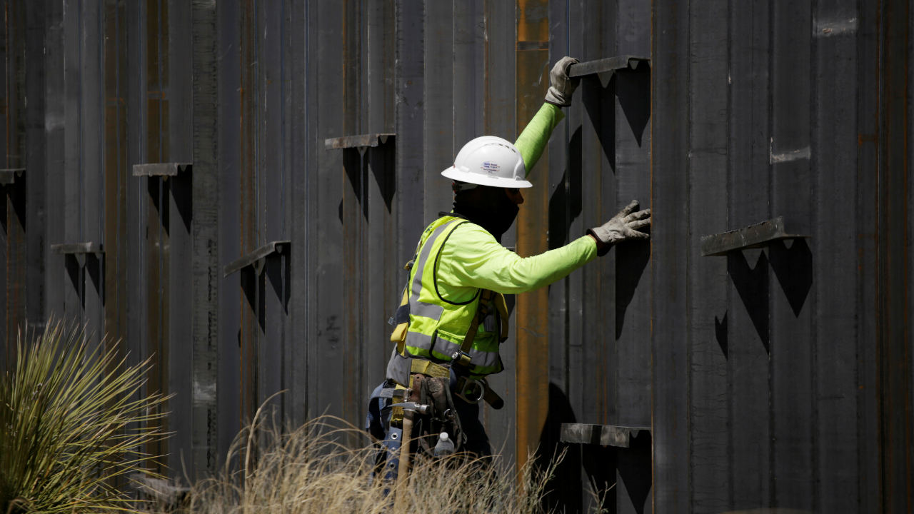 A construction worker talks to a colleague at a new section of bollard wall in Santa Teresa, New Mexico, as seen from the Mexican side of the border in San Jeronimo, on the outskirts of Ciudad Juarez, Mexico. (Reuters)