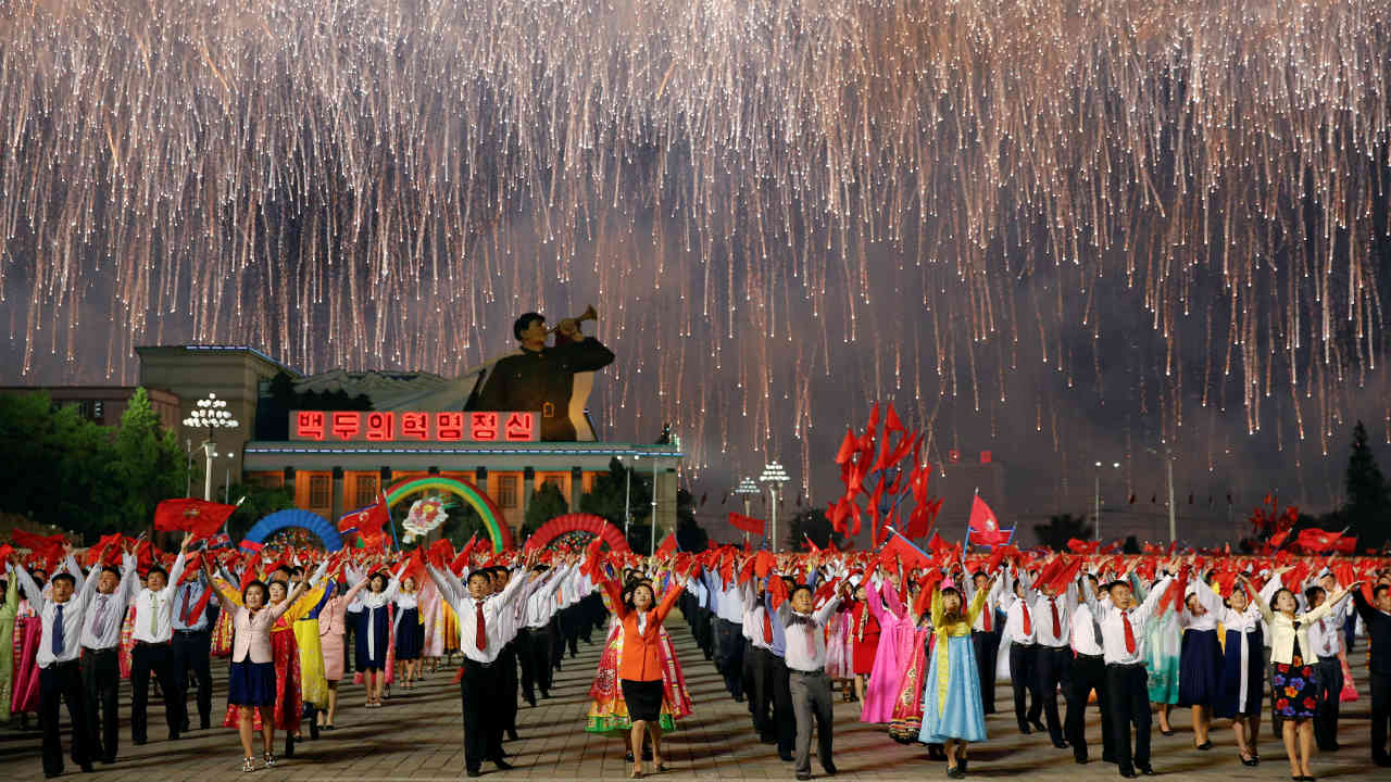 Fireworks explode over participants in a mass dance in the capital's main ceremonial square, a day after the ruling Workers' Party of Korea party wrapped up its first congress in 36 years, in Pyongyang. (Photo: Reuters)