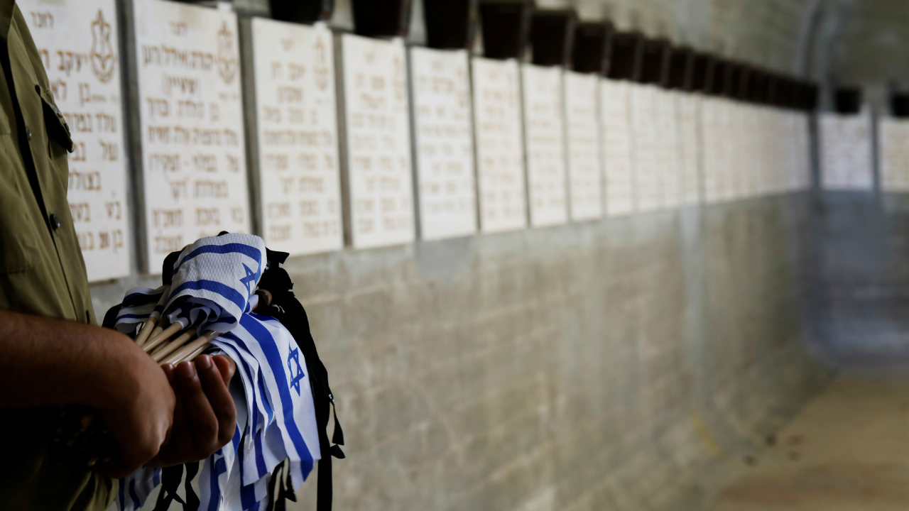 An Israeli soldier holds Israeli flags as he stands next to the names of crew members of the Dakar submarine at the Mount Herzl military cemetery ahead of Memorial Day, in Jerusalem (Photo: Reuters)