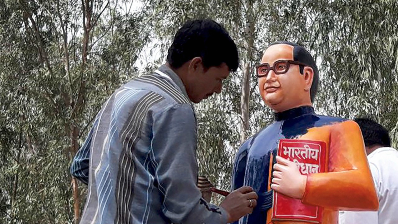 A BSP worker paints the newly constructed statue of BR Ambedkar in blue in Badaun. The saffron-statue raised controversy as Ambedkar's statues have always been shown in a blue coat. (PTI)