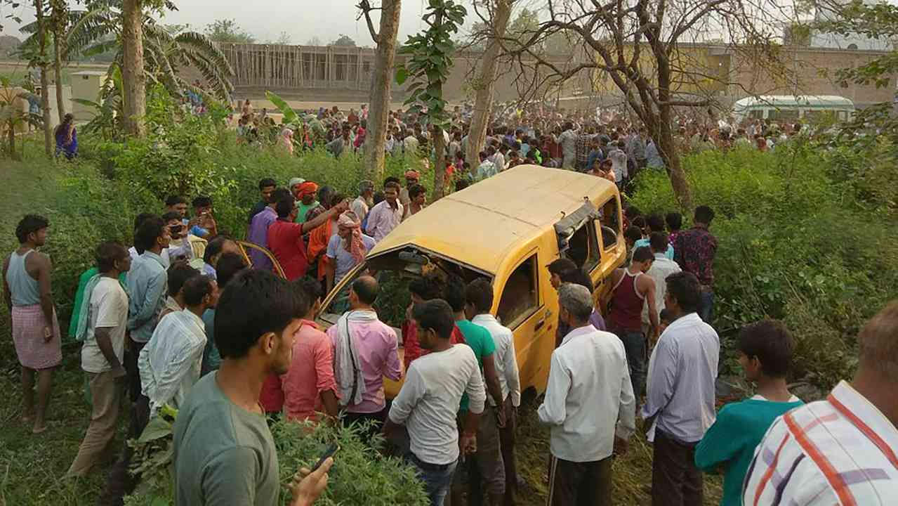 People gather around the mangled school van after it collided with a moving train in Kushinagar, Uttar Pradesh, on Thursday morning. (PTI)