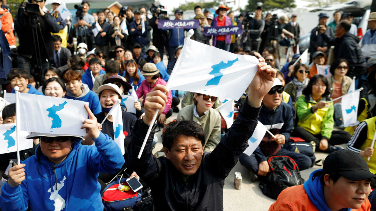 People hold the Korean unification flag during the inter-Korean summit, near the demilitarized zone separating the two Koreas, in Paju, South Korea. (Image: Reuters)