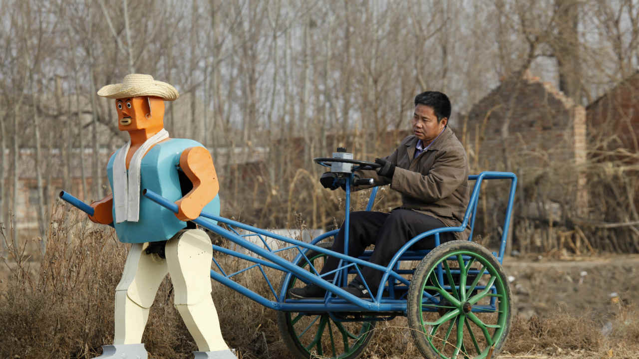 Farmer Wu Yulu drives his rickshaw pulled by a his home-made walking robot near his home in a village at the outskirts of Beijing January 8, 2009. This robot is the latest and largest development of hobby inventor Wu, who started to build robots in 1986, made of wire, metal, screws and nails found in rubbish sites. (REUTERS)