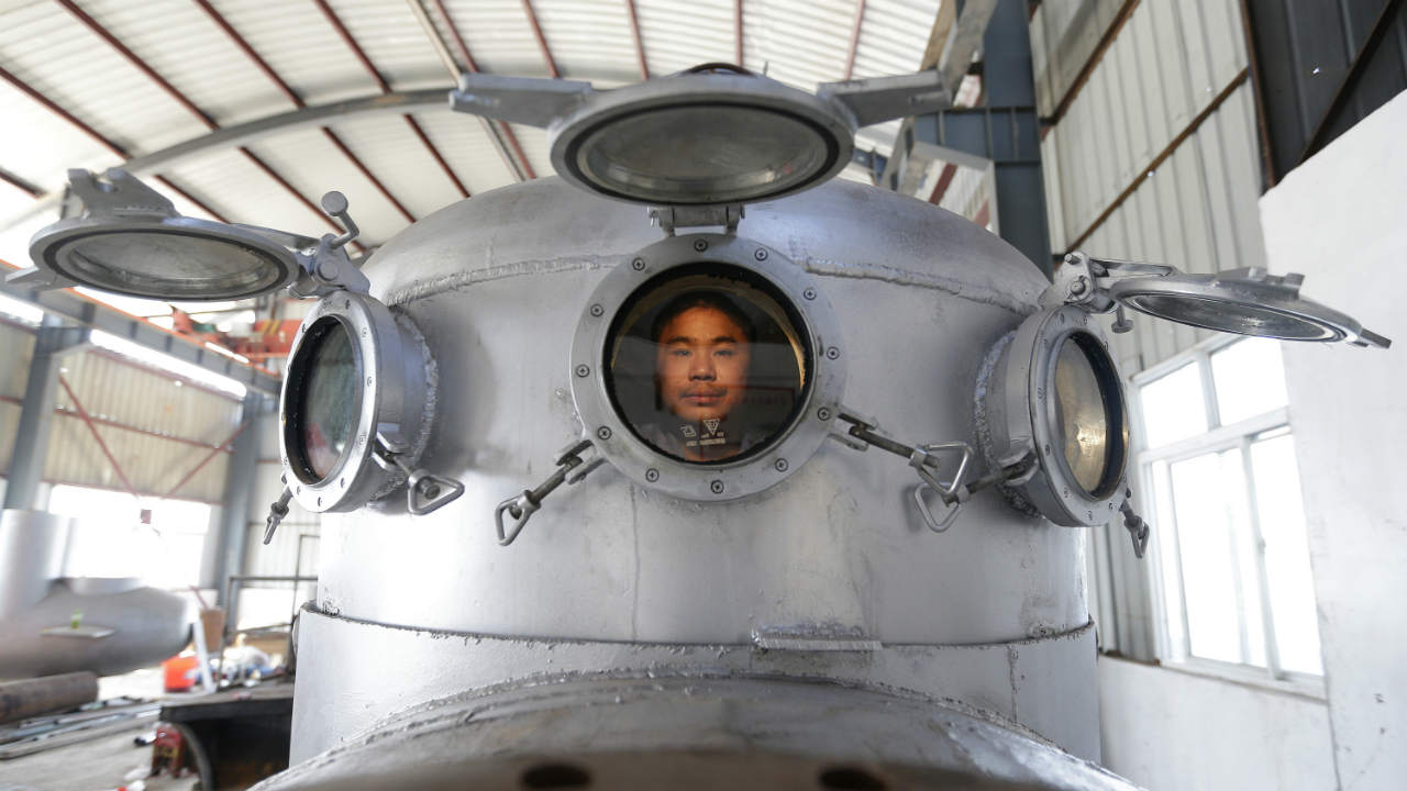 Zhang Wuyi sits in his newly made multi-seater submarine at his new workshop near an artificial pool in Wuhan. Zhang, a 37-year-old local farmer, who is interested in scientific inventions, has independently made seven miniature submarines with several fellow engineers, one of which was sold to a businessman in Dalian at a price of 100,000 yuan (USD 15,855) last October. The submarines, mainly designed for harvesting aquatic products, such as sea cucumber, have a diving depth of 20-30 metres (66-98 feet), and can travel for 10 hours, local media reported. (REUTERS)