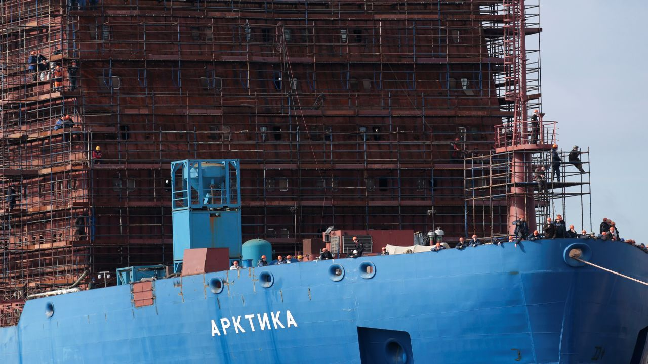 """Workers are seen on the nuclear atomic icebreaker """"Arktika"""" operated by Rosatomflot watch the as Akademik Lomonosov is being towed to the Atomflot base in Murmansk for nuclear fuel loading, in St Petersburg. (Image: Reuters)"""
