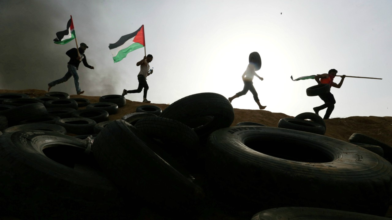 Palestinian protesters run during clashes with Israeli troops at Israel-Gaza border, in the southern Gaza Strip. (REUTERS)