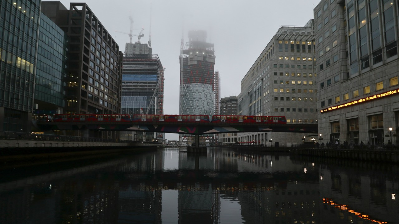 A DLR train crosses a bridge in front of construction work in the early morning mist in London's Canary Wharf financial district, London, Britain. (Image: Reuters)