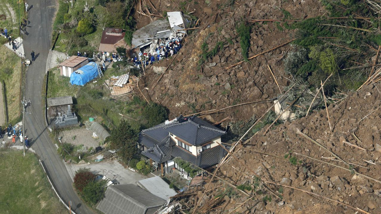 Rescue workers search for missing people at the site where houses were buried in a landslide at Yabakei town in Nakatsu, Oita Prefecture, southwestern Japan. (Image: Kyodo/via Reuters)