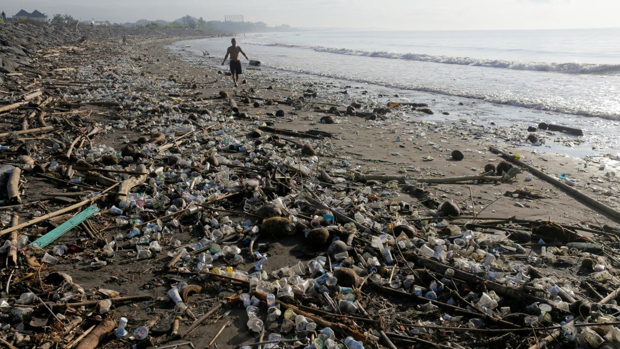 A local resident walks along a section of Matahari Terbit beach covered in plastic and other debris washed ashore by seasonal winds near Sanur, Bali, Indonesia. (Image: Reuters)