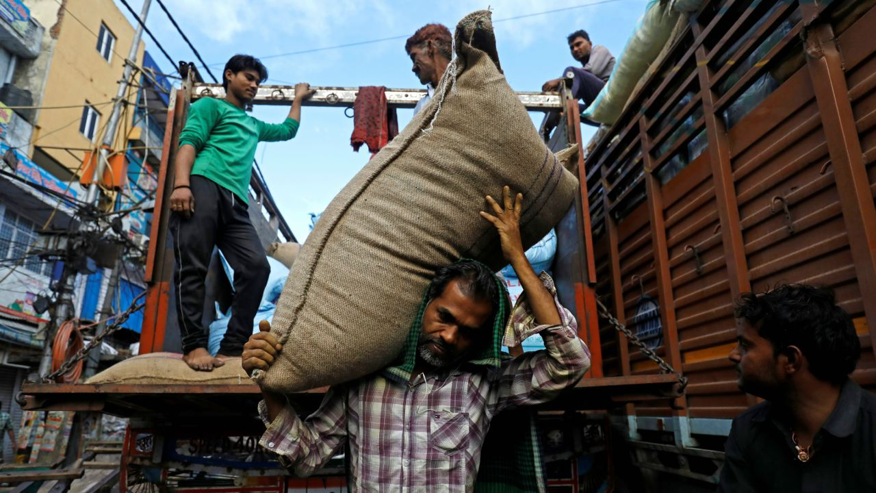 Labourers unload sacks of spices at the spice market in the old quarters of Delhi, India. (Image: Reuters)