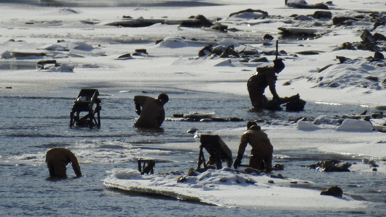North Koreans are photographed from the Chinese side of the border as they go about their chores in the freezing Yalu River. (Image: Reuters)