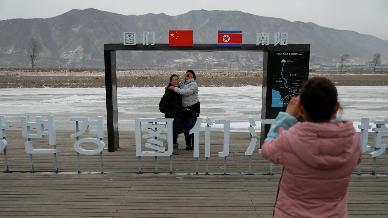 People have their picture taken with North Korea in the background, in Tumen, China. (Image: Reuters)