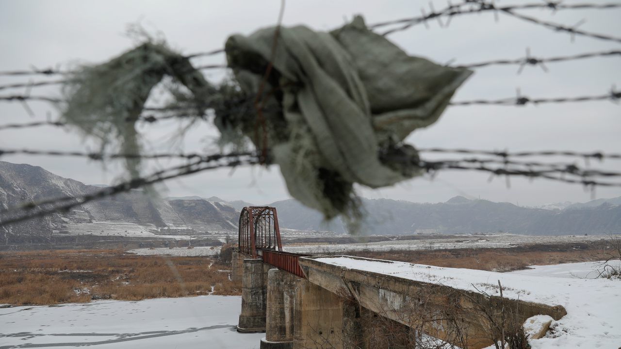 A piece of cloth is used to make a gap between a barbed-wire fence near the closed bridge over the Yalu River on the Chinese side of the border along North Korea between the towns of Ji'an and Linjiang in China. (Image: Reuters)
