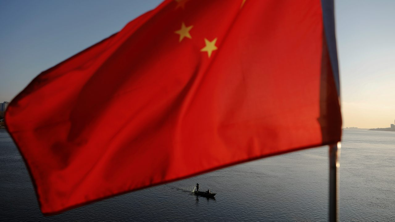 North Korean fishermen are seen as a Chinese flag flutters from the Broken Bridge as the sun sets over the Yalu River between the North Korean town of Sinuiju and Dandong in Liaoning Province, China. (Image: Reuters)