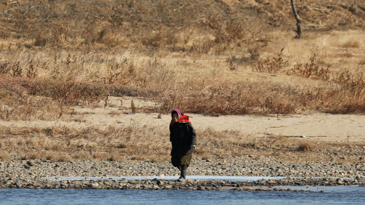 A North Korean woman is photographed from the Chinese side of the border north of Dandong, China as she walks on the banks of the Yalu River just north of Sinuiju, North Korea. (Image: Reuters)