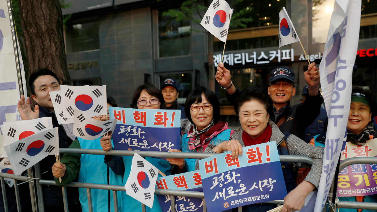 Supporters hold South Korean flags and signs while waiting for a convoy transporting South Korean President Moon Jae-in to leave the Presidential Blue House for the inter-Korean summit, in Seoul, South Korea. (Image: Reuters)