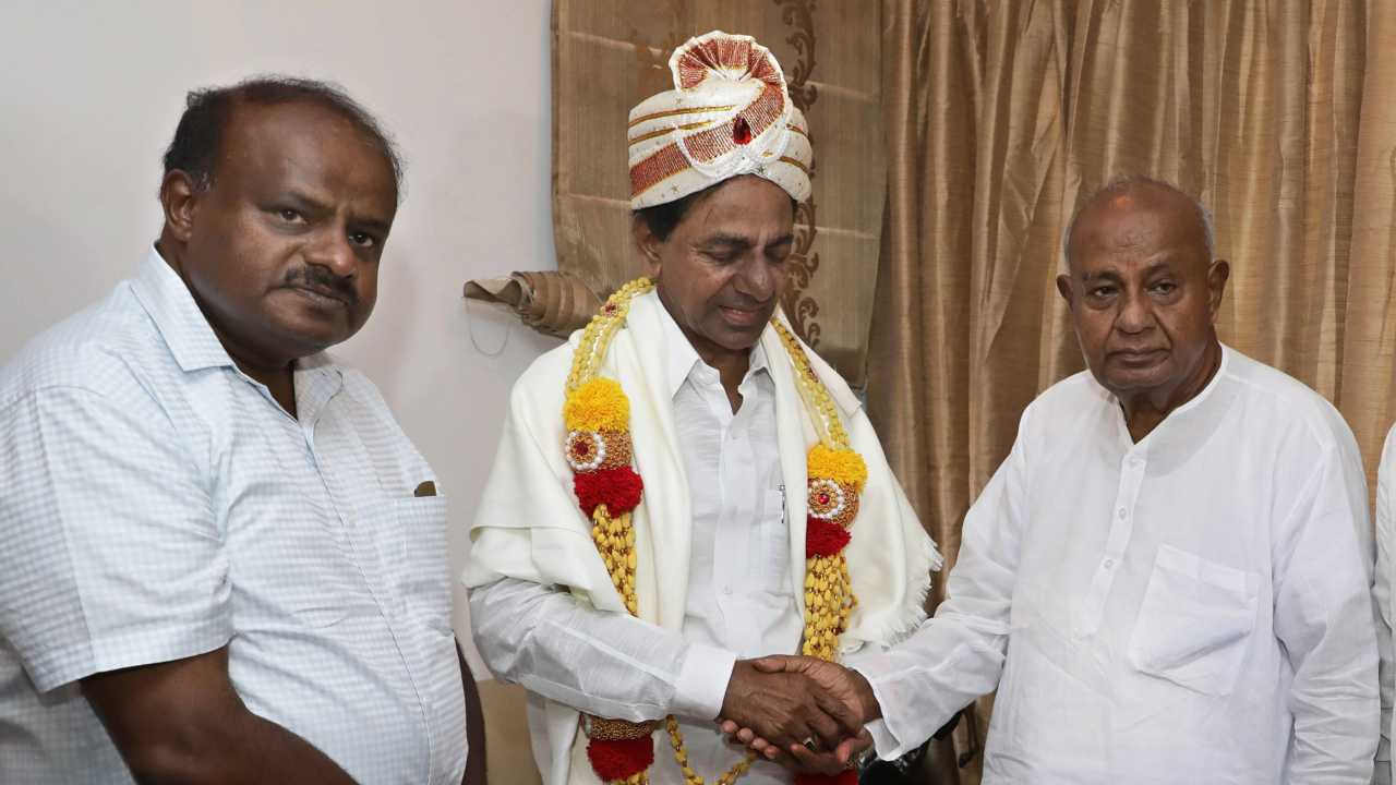 Telangana Chief Minister K Chandrashekhar Rao presented with Mysore Peta by JD(S) supremo and former prime minister H D Deve Gowda as former Karnataka chief minister H D Kumaraswamy looks on, during a meeting in Bengaluru on 14th April 2018. (PTI photo)