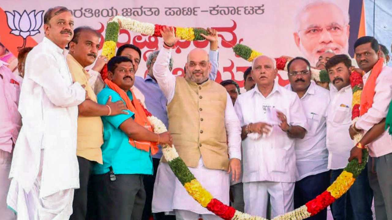 "BJP National President Amit Shah with BS Yeddyurappa at a public meeting on the concluding day of ""Musti Dhanya Sangraha Abhiyan"" in Abbigeri Village, Gadag district of Karnataka on 12th April 2018. (PTI Photo)"