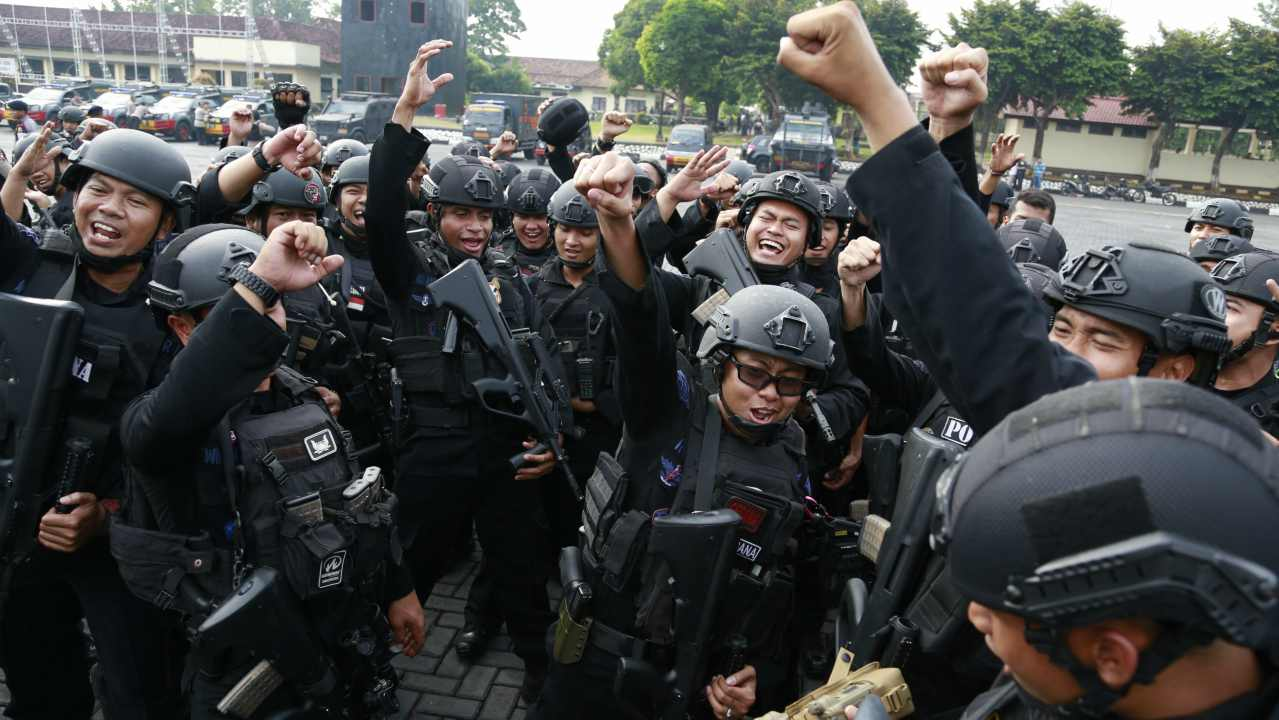 Officers cheer after a briefing at the headquarters of elite police unit Mobile Brigade in Depok, West Java. Indonesia's top security minister said dozens of Islamic militants who took over the detention center inside the compound near Indonesia's capital, killing a number of officers, have surrendered to police. (AP/PTI)
