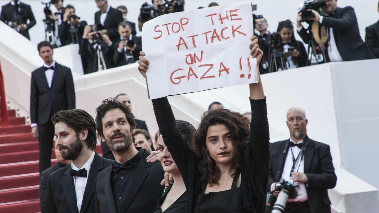 """Lebanese actress Manal Issa, from """"My Favorite Fabric"""" holds a sign that reads """"Stop the Attack on Gaza"""" at the premiere of the film """"Solo: A Star Wars Story"""" at the 71st international film festival, Cannes, southern France. Israeli soldiers shot and killed 59 Palestinians and wounded hundreds in mass protests on the Gaza border on Monday. (AP/PTI)"""