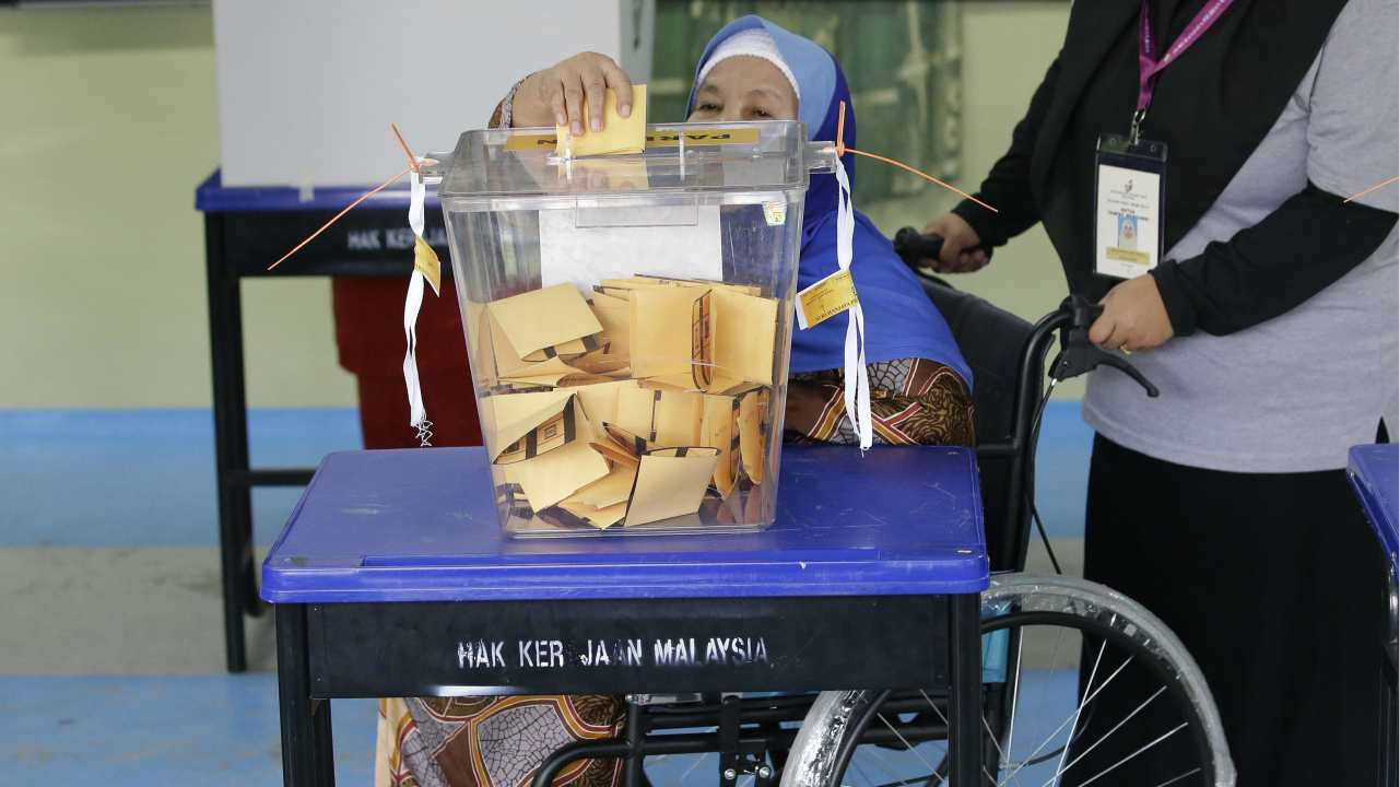A woman on a wheelchair is assisted as she casts her vote for the general election, in Pekan, Pahang state, Malaysia. Malaysia's general elections will determine if scandal-plagued Prime Minister Najib Razak's coalition can extend nearly 61 years of unbroken rule against an unprecedented challenge led by the former strongman Mahathir Mohamad. (AP/PTI)