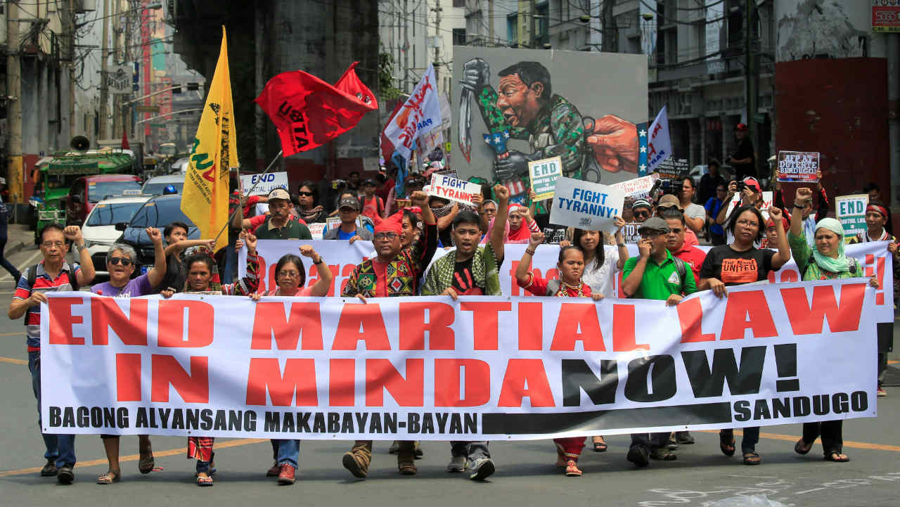 Activists display a banner and a mural of President Rodrigo Duterte to denounce the declaration of martial law in Mindanao island, one year after Islamic militants occupied parts of Marawi during a protest outside the presidential palace in Metro Manila, Philippines. (Reuters)