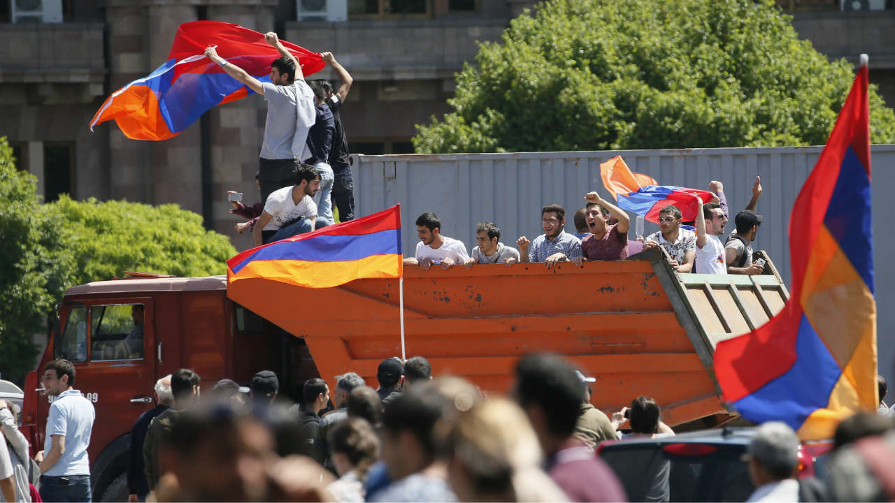 Armenian opposition supporters wave national flags as they ride on a truck after protest movement leader Nikol Pashinyan announced a nationwide campaign of civil disobedience, at Republic Square in Yerevan, Armenia. (Reuters)