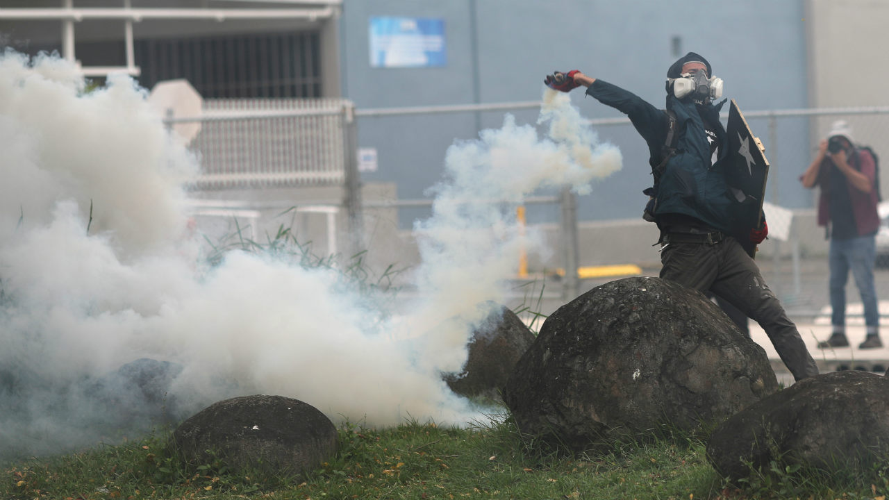 A demonstrator throws a tear gas canister during clashes with police at a May Day protest against austerity measures, in San Juan, Puerto Rico. (Reuters)