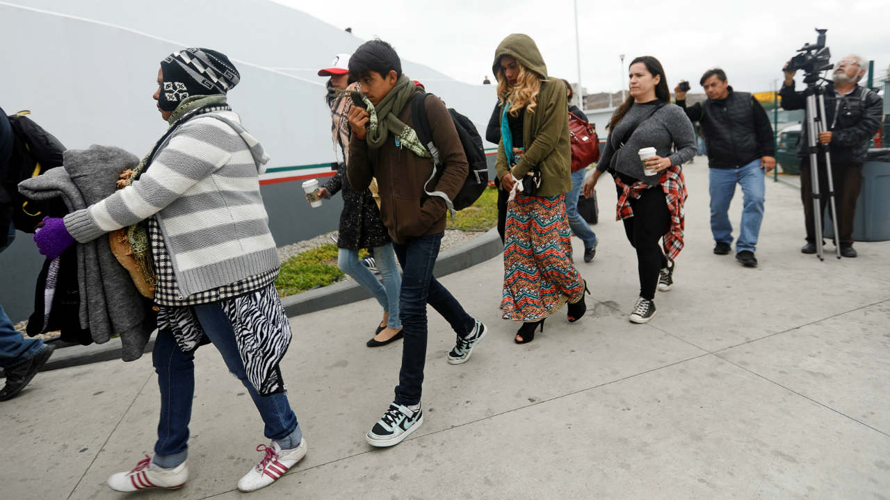 Members of a caravan of migrants from Central America enter the United States border and customs facility, where they are expected to apply for asylum, in Tijuana, Mexico. (Reuters)