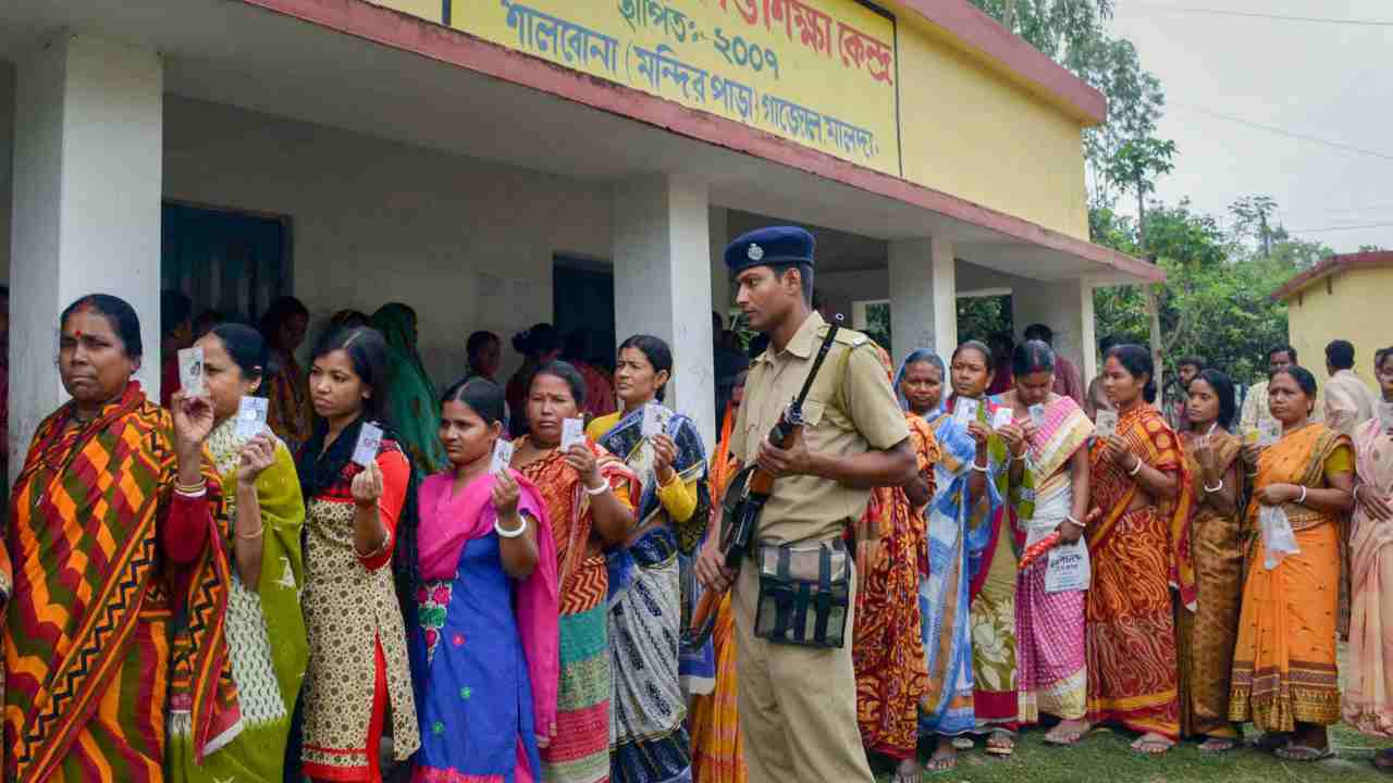 Voters stand in a queue to cast their vote during re-polling of Panchayat elections at Shikshak Pally booth, Gazole in Malda district of West Bengal on Wednesday. (PTI)
