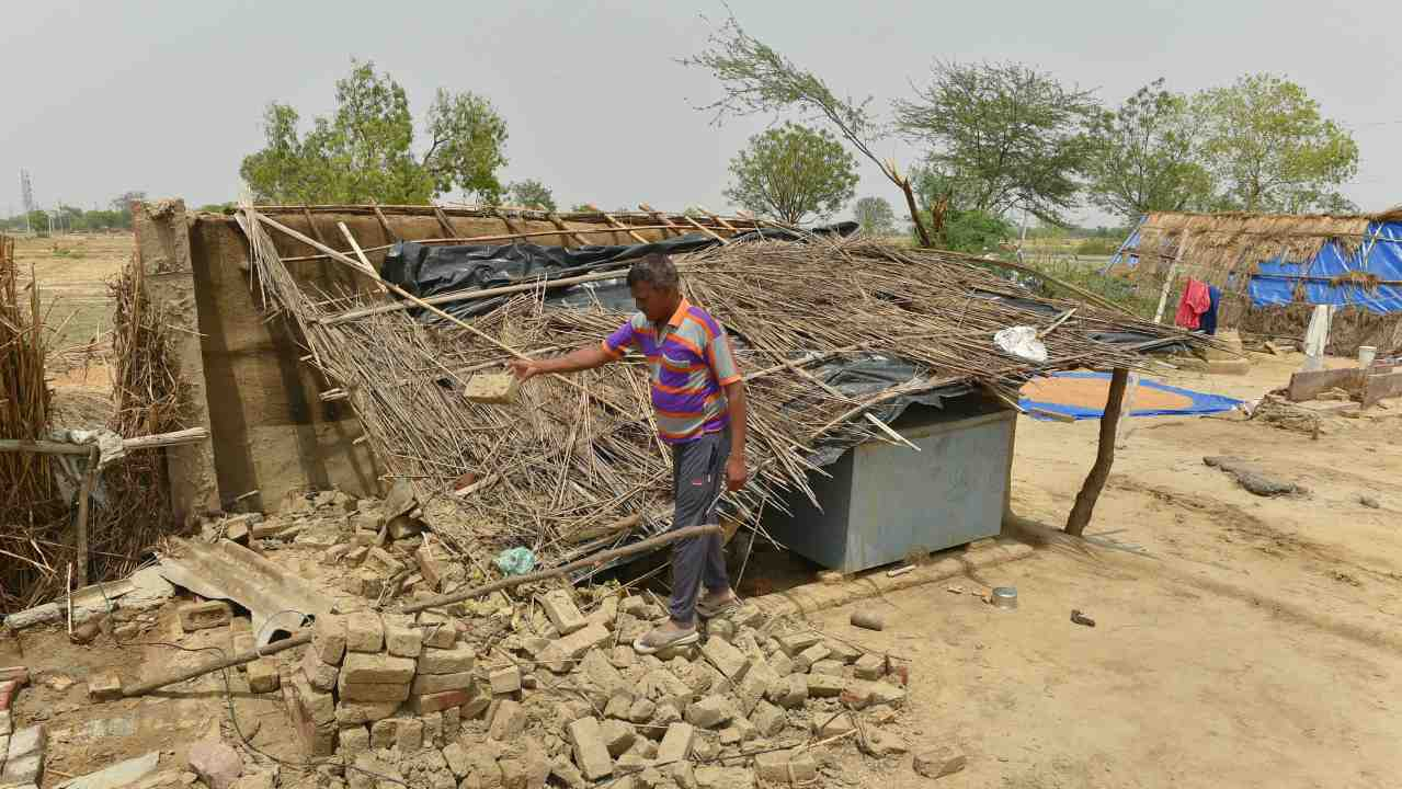 A man shows his thatched house, damaged in Wednesday's massive storm, at Cheet village in Agra district on Friday. (PTI)